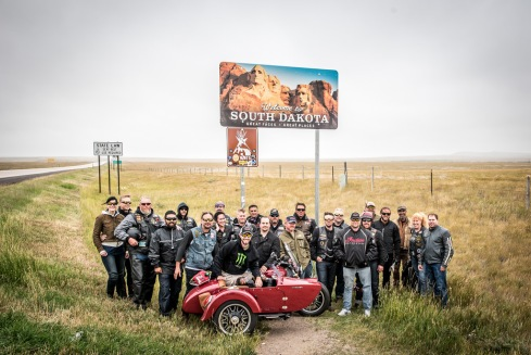 group of people and motorcycle with a sign