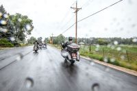 Motorcycle riders and sidecar riding in the rain on a highway road.