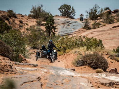Motorcycle sidecar Ural rides off road in Moab Utah with motorcycle in background on trail.