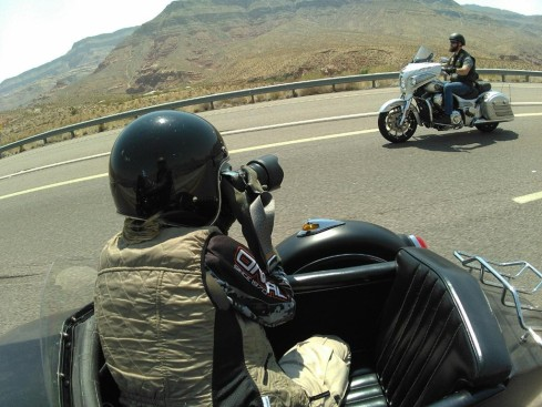 Camera woman shoots photos of a motorcycle on a highway, from a sidecar.