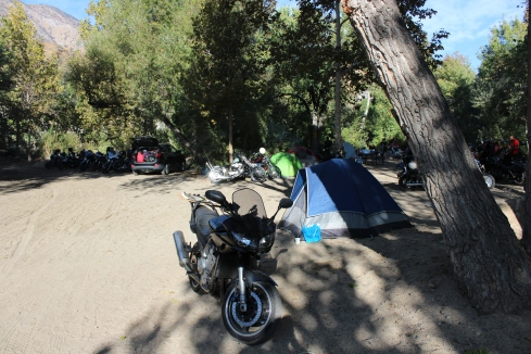 A motorcycle next to a tent in a campground by a river