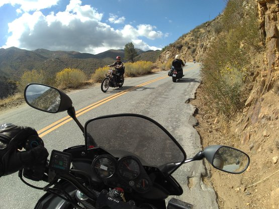 onboard a motorcycle on a road in the mountains, looking at othr motorcyclists