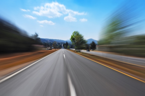 a road leads to the horizon, blurred with speed