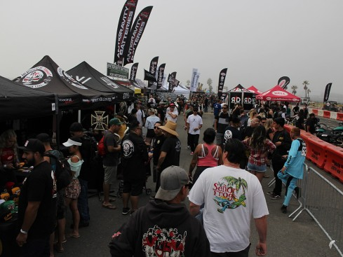 A crowd of people on the beach at a motorcycle event