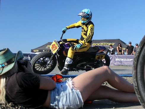 a photographer takes pictures of a flat track motorcycle race