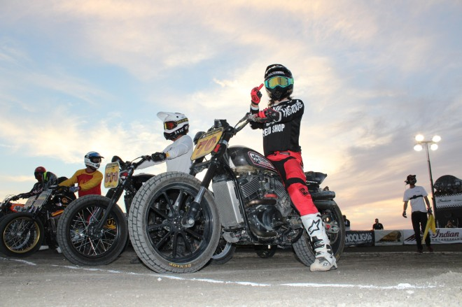 a Harley Davidson motorcycle hooligan flat track racer waits on the strating line while gesturing.