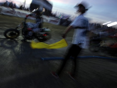 motorcycle racing by a waving yellow flag at a flat track racing event