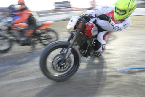 A Ducati motorcycle flat track hooligan racer negotiates a turn on a race track.
