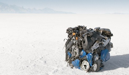 A Buell motorcycle in the desert on a dry lake bed, crushed into a cube