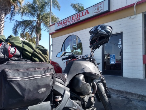 buell motorcycle with saddlebags parked in front of a taco restaurant