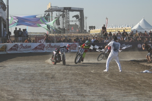 motorcycle flat tack racers sliding sideways across finish line