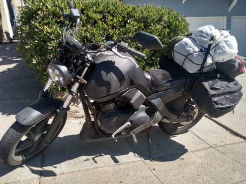 a black motorcycle loaded with luggage small buell blast